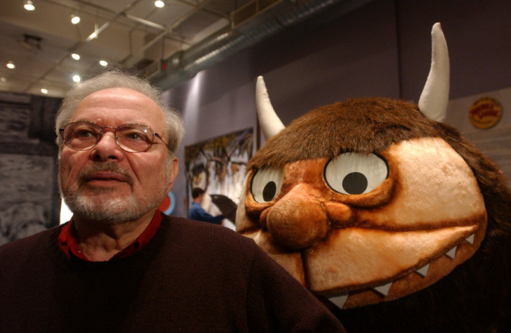 Standing with a character from his book 'Where the Wild Things Are,' author and illustrator Maurice Sendak speaks with the media January 11, 2002 before the opening of an exhibition entitled, 'Maurice Sendak In His Own Words and Pictures,' at the Childrens Museum of Manhattan in New York City