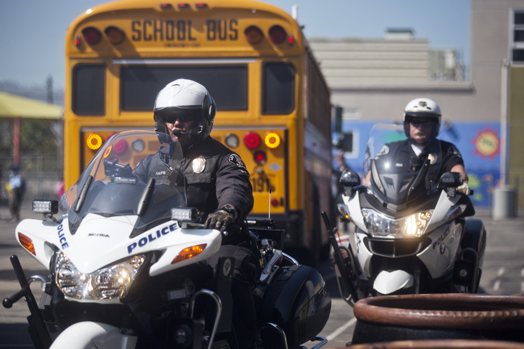 LAPD aids in the relocation of students at George De La Torre Junior Elementary School on Tuesday morning, Sept. 23, after a fire broke out nearby at the Port of Los Angeles on Monday night.