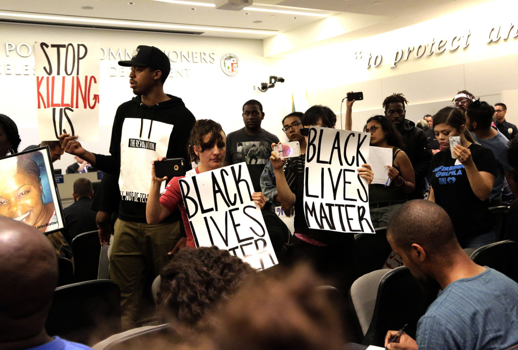 Black Lives Matter protesters demonstrate inside the Board of Police Commissioners meeting in Los Angeles on Tuesday, Oct. 4, 2016. Los Angeles police released surveillance video Tuesday showing an 18-year-old black suspect running from police while holding what appears to be a gun in his left hand just before he was fatally shot by officers in a death that has generated rowdy protests.