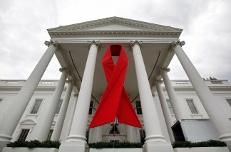 A red ribbon is hung between columns of the White House to commemorate World AIDS day. Aid groups are warning that, due in part to the ongoing global economic slowdown, donor money for AIDS research and treatment around the globe is slipping precisely when those funds are needed the most.