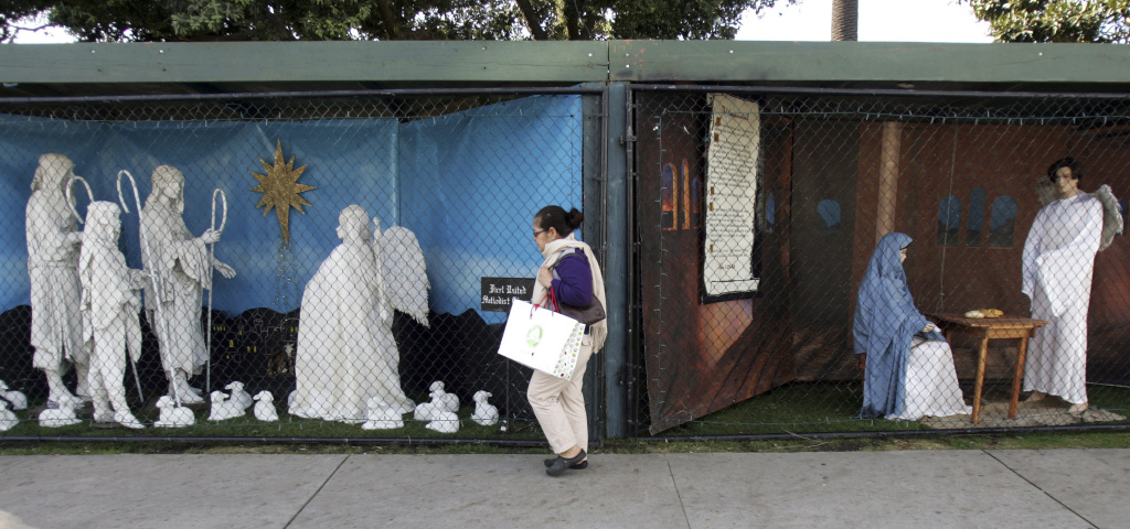 A woman walks past two of the traditional displays showing the Nativity scene along Ocean Avenue at Palisades Park in Santa Monica, California, on Dec. 13, 2011.