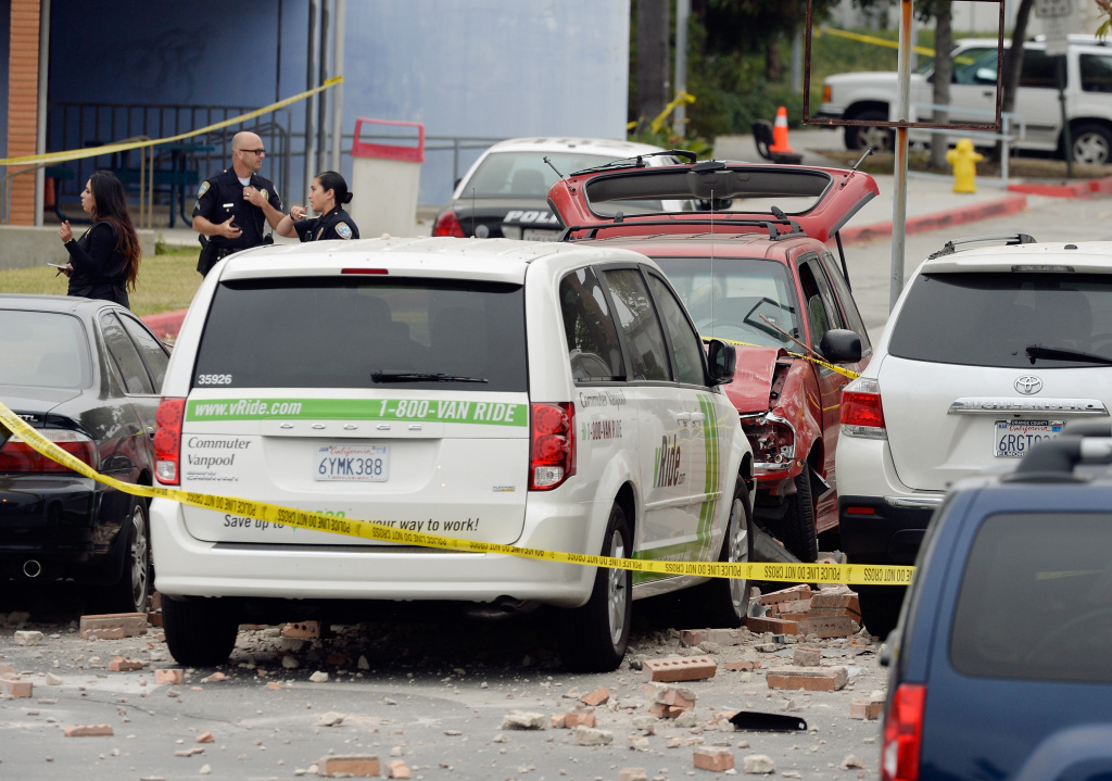 Law enforcement personal investigate the shooting scene where an SUV crashed through the wall of a parking lot and hit several cars across the street from the Santa Monica College.