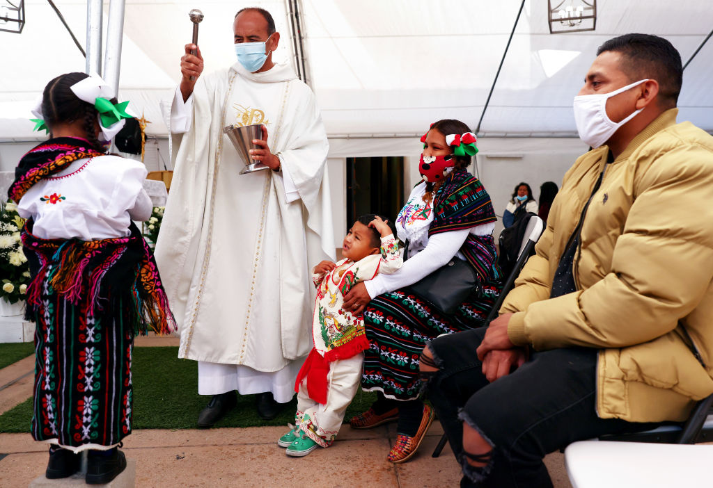 The Rev. Arturo Corral sprinkles holy water following Mass marking the Feast of Our Lady of Guadalupe December 12, 2020 in Los Angeles, California.