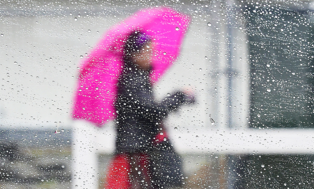 Raindrops are seen on a vehicle's window as a woman walks by using an umbrella under heavy rainfall in Los Angeles on March 21, 2018.