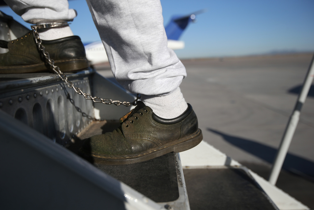 A Honduran immigration detainee, his feet shackled and shoes laceless as a security precaution, boards a deportation flight to San Pedro Sula, Honduras.