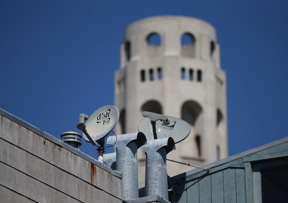 A Dish Network satellite dish (L) is mounted next to a DirecTV dish on the roof of an apartment building on April 15, 2013 in San Francisco, California.