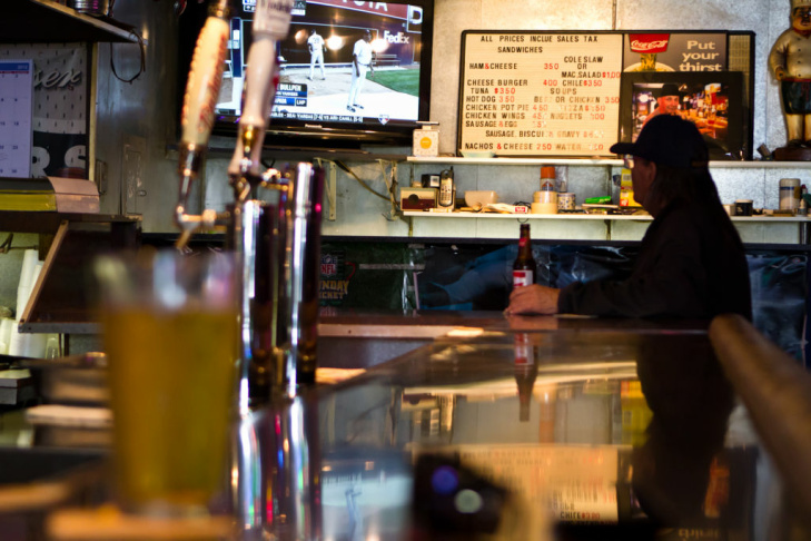 A customer watches televison as he drinks his beer in King Eddy Saloon.