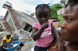 A Haitian earthquake survivor holds her child near a collapsed building in Jacmel on January 19, 2010 a week after the country was shattered by a massive 7.0-magnitude quake. The Haitian government said 70,000 bodies had been buried in mass graves since the earthquake flattened much of the impoverished Caribbean nation on January 12, triggering a massive humanitarian crisis. Officials fear the eventual death toll could top 200,000.