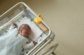 A newborn baby lies in bed in a hospital maternity ward.