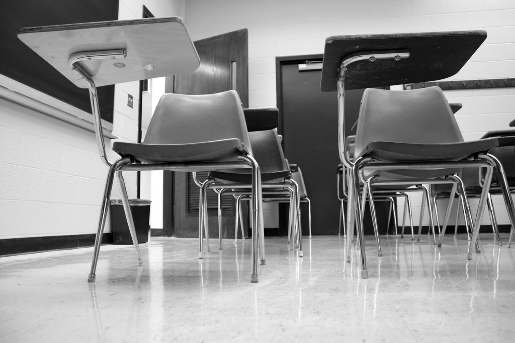 Empty school desk chairs sit in an elementary school classroom