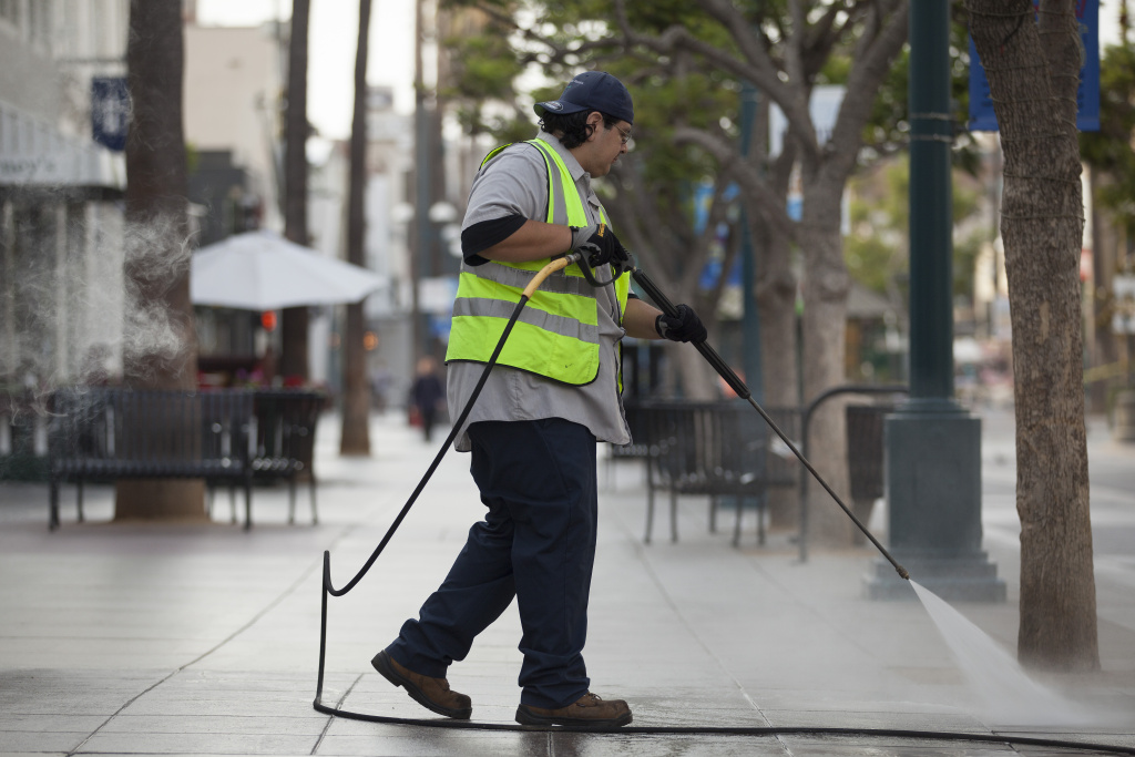 A Santa Monica city employee washes down the Promenade early Tuesday morning, July 15, 2014. The Promenade is pressured washed daily but much of the water is reclaimed and used to water local parks, a maintenance supervisor said.