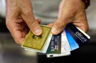 Alain Filiz shows off some of his credit cards as he pays for items at Lorenzo's Italian Market on May 20, 2009 in Miami, Florida. File photo.