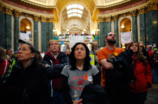 Protestors watch as the State Assembly discusses controversial legislation inside the Wisconsin State Capitol February 22, 2011 in Madison, Wisconsin.