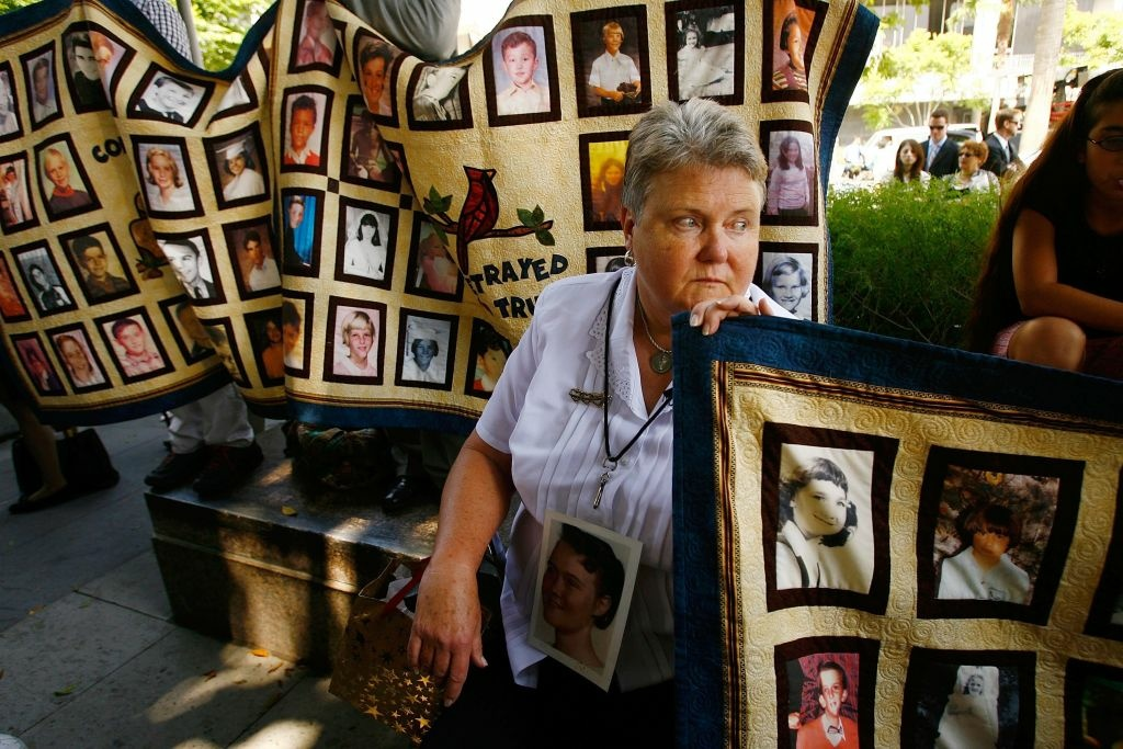 Victoria Martin, an alleged victim of sexual abuse by a priest, holds a quilt with faces of other victims at the Los Angeles County Courthouse on July 16, 2007.