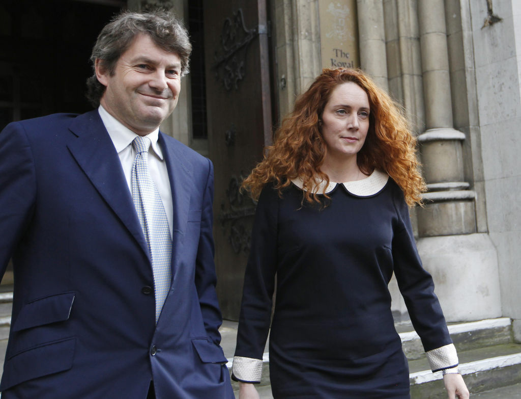 Rebekah Brooks, former chief executive of News International and her husband Charlie Brooks leaving the High Court in London after giving evidence to the Leveson Inquiry. Brooks said Tuesday May 15, 2012 she and her husband will face charges over Britain's tabloid phone hacking scandal. Brooks, 43, said Tuesday in a statement that she will be prosecuted over allegations of obstruction of justice.