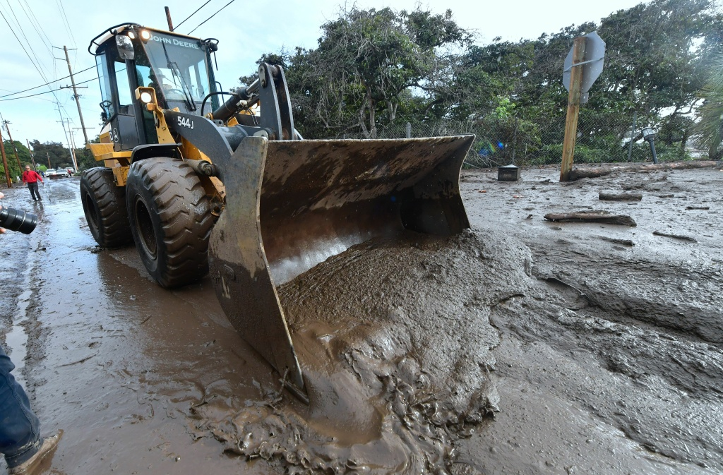A bulldozer clears mud off the road near a flooded section of US 101 freeway near the San Ysidro exit in Montecito, California on January 9, 2018.
