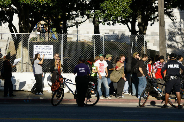 Protesters from Occupy LA walk down 1st Street in front of the closed-off City Hall park that they camped in for nearly two months before being removed on Tuesday.