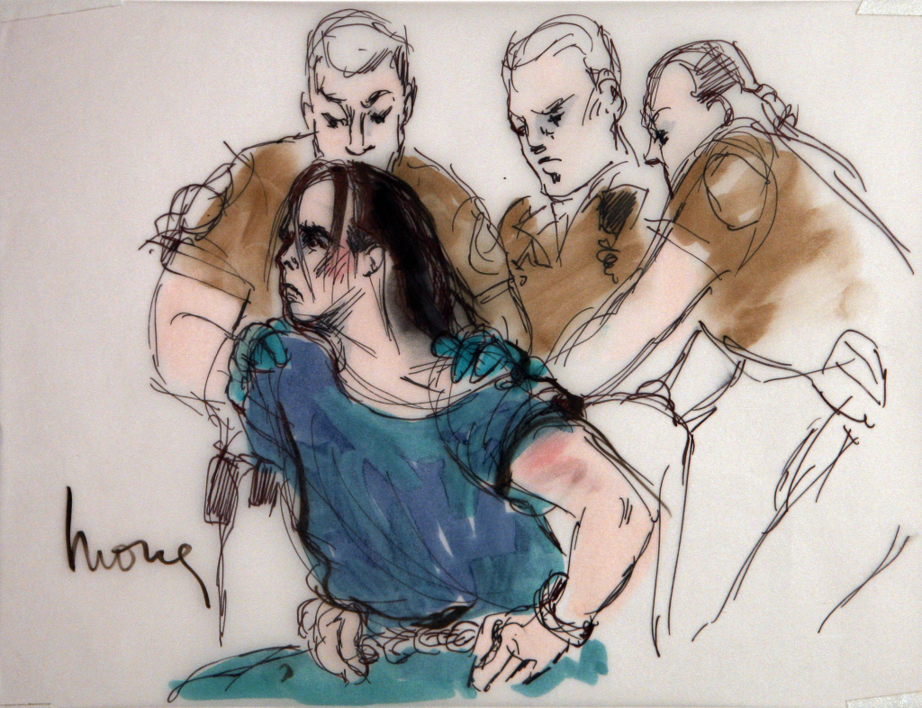 In this courtroom sketch, Harry Burkhart, a native of Germany who has been living in Los Angeles and is suspected in a series of arson fires, is restrained by guards as he alternately tries to stand and sit during his arraignment in Los Angeles Superior Court, Wednesday, Jan. 4, 2012 in Los Angeles. Burkhart was charged with 37 counts of arson in connection with a rash of fires that terrorized Los Angeles over the New Year's weekend. (AP Photo/Mona Shafer Edwards)