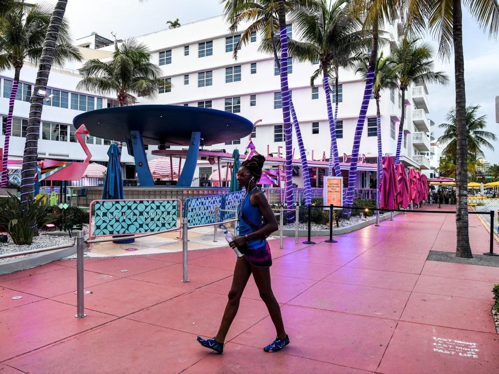 A woman walks past a closed restaurant in Miami Beach, Florida on Tuesday, amid the coronavirus pandemic.
