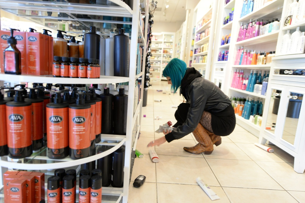 Employee Paula Anania cleans up hair care products that were knocked off the shelf in a beauty supply store in the Encino area of Los Angeles after a 4.4 earthquake jolted the area March 17, 2014.