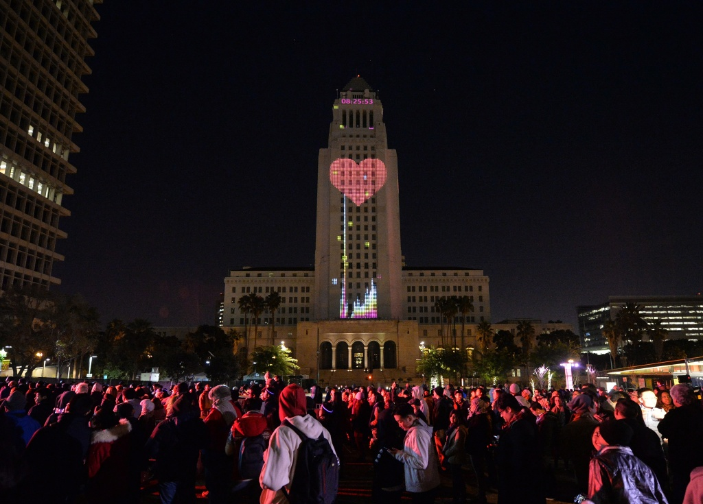 City Hall is lit by two dimensional projected images while people celebrate the New Year at the Grand Park's N.Y.E.L.A. event in downtown Los Angeles on December 31, 2014.  The free event which attracted nearly 30,000 party-goers hosted bands on three stages and shutdown a large section of downtown Los Angeles.