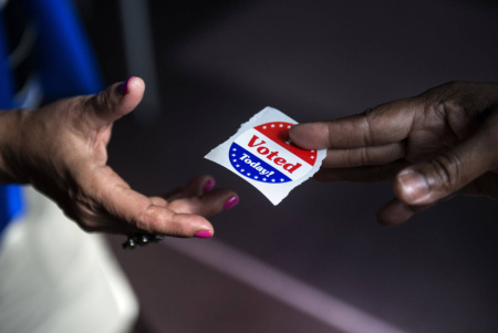 A poll worker hands out 'I Voted' stickers.