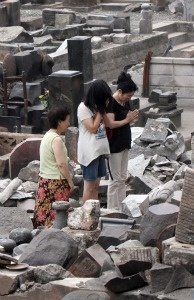 A family prays for victims of the tsunami and earthquake before a broken tombstone at a graveyard at Otsuchi town, Iwate prefecture on August 11, 2011.