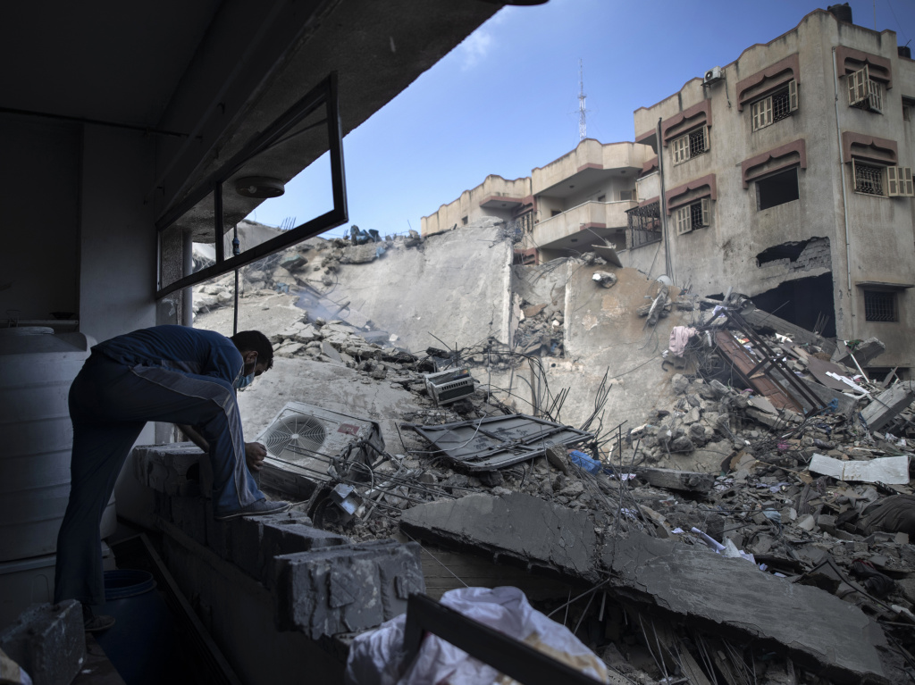 A Palestinian man inspects the damage of a six-story building destroyed by an early morning Israeli airstrike, in Gaza City on May 18, 2021.