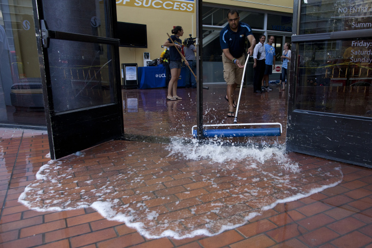 Water and debris covers the court inside Pauley Pavilion at UCLA after a water main broke on Sunset Boulevard. Crews worked to mitigate the flooding and began removing water from the recently renovated sports arena.