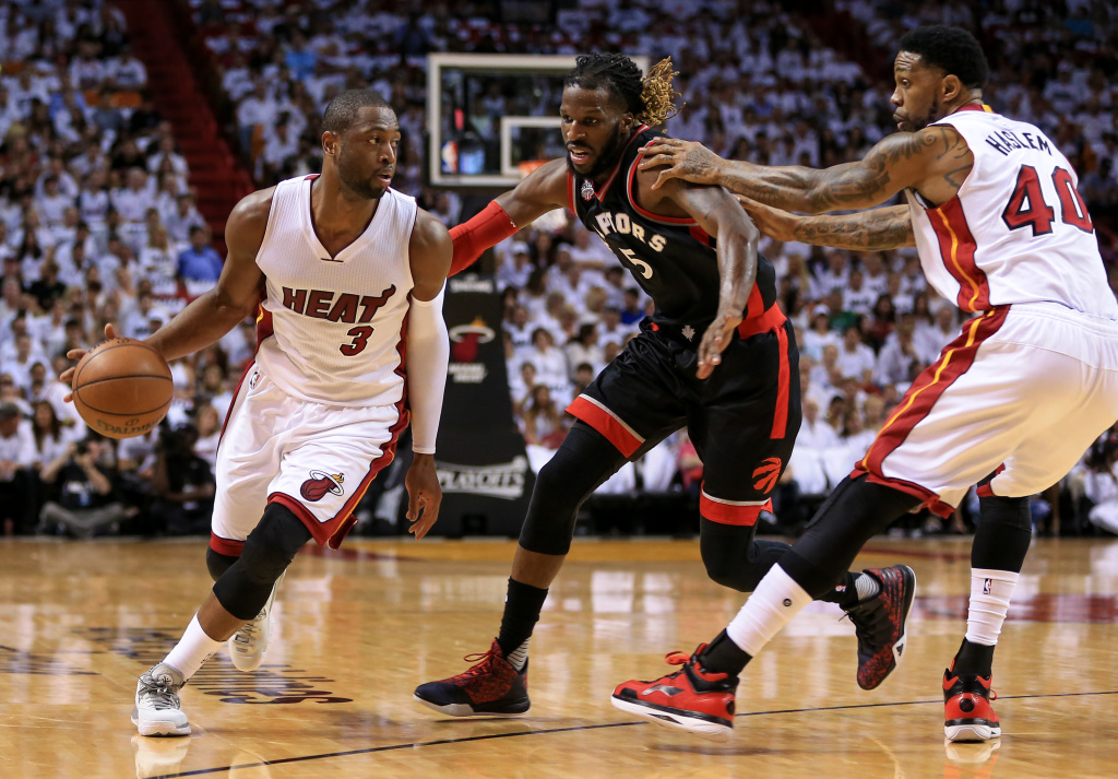 Dwyane Wade #3 of the Miami Heat drives past DeMarre Carroll #5 of the Toronto Raptors on a pick set by Udonis Haslem #40 during the first quarter of the game at American Airlines Arena.