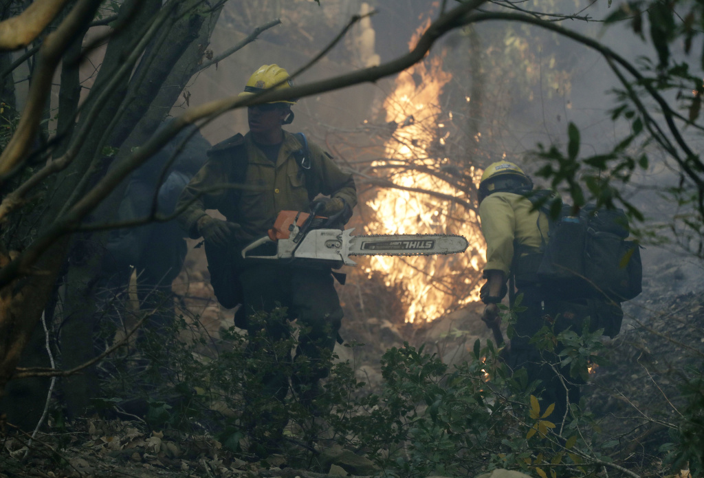 Firefighters from Kern County work to put out hot spots during the Thomas Fire in Montecito, Calif., in this Saturday, Dec. 16, 2017 file photo.