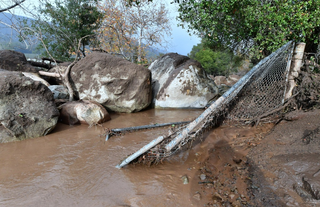 Boulders carried down nearby hillsides from the overnight rains remain beside a broken fence in Carpinteria, California on January 9, 2018.  Mudslides unleashed by a ferocious storm demolished homes in southern California and killed at least 13 people, police said Tuesday. / AFP PHOTO / FREDERIC J. BROWN        (Photo credit should read FREDERIC J. BROWN/AFP/Getty Images)