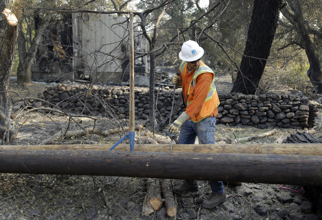 A PG&E worker replaces power poles destroyed by wildfires on Wednesday, Oct. 18, 2017, in Glen Ellen, California.