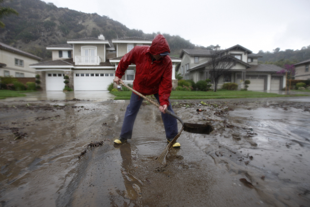 Bob Lavezzari clears ashen mud from his street in a neighborhood threatened with a possible major mudslide below a burned hillside as a storm brings rain in the midst of record drought.