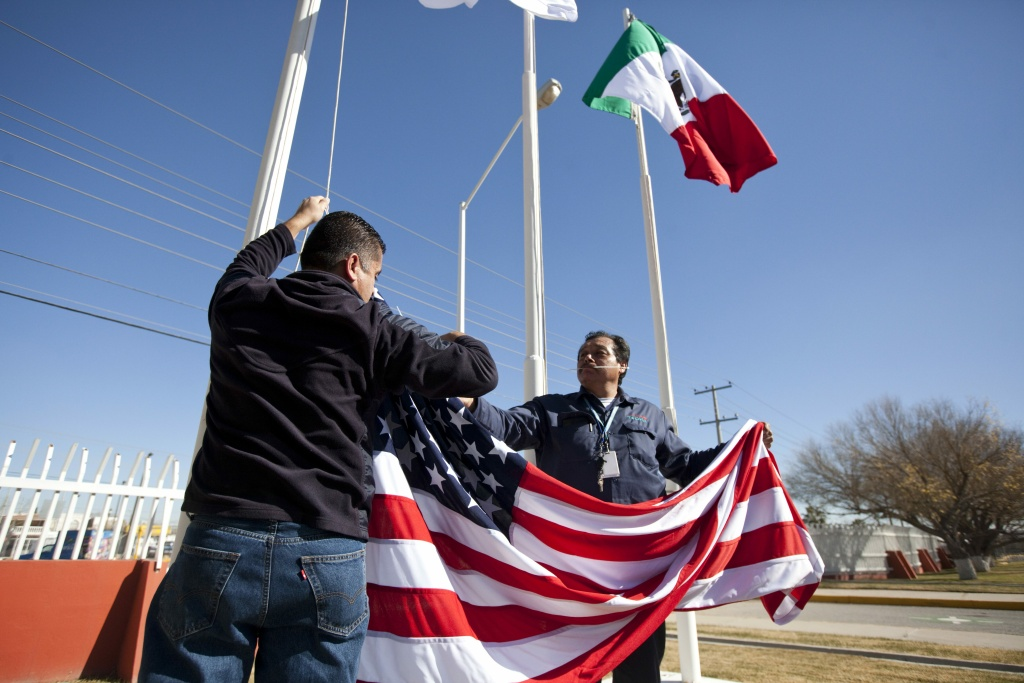 File: In this Friday, Dec. 27, 2013 photo, workers at one of maquiladoras of the TECMA group prepare to raise the U.S. flag along with the Mexican and TECMA flags in Ciudad Juarez, Mexico. TECMA currently has 14 maquiladora plants in Ciudad Juarez. With the implementation of the North American Free Trade Agreement twenty years ago, many North American and international companies have moved their manufacturing to Mexico at a lower cost and while a majority of Mexicans have seen little benefit in income.