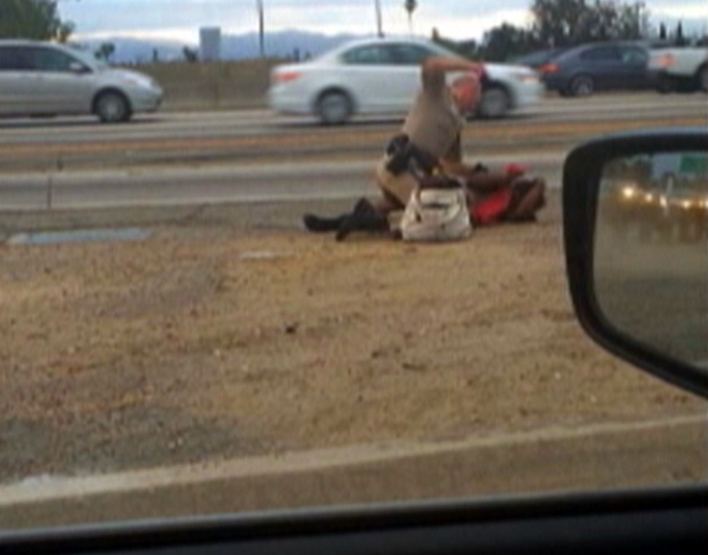 In this July 1, 2014 image made from video provided by motorist David Diaz, a California Highway Patrol officer straddles Marlene Pinnock while punching her in the head on the shoulder of a Los Angeles freeway.