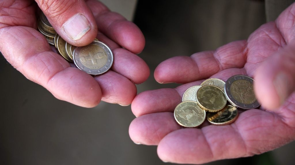 A Cypriot man held some  coins in Nicosia on Sunday. He and others on the island nation were watching anxiously as world leaders put together a bailout package for Cypriot banks.