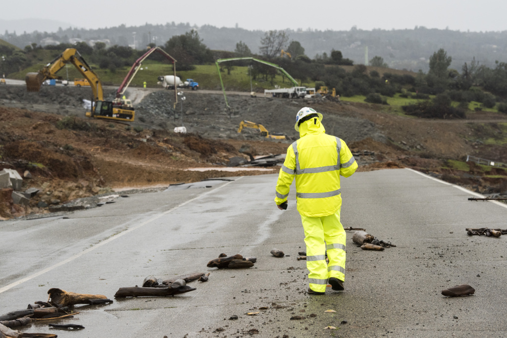 A worker walks down the damaged roadway near the Oroville Dam emergency spillway on February 17, 2017 in Oroville, California.