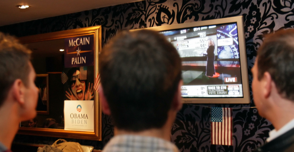 Revellers watch the screens in Yates' bar in Leicester Square, London on November 4, 2008 as US news network CNN become the first company to use a holographic projection to interview a journalist during the US election.