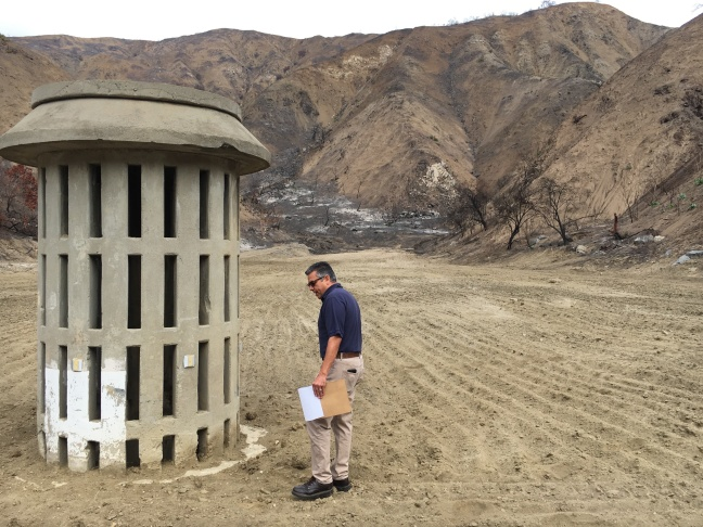 Civil Engineer Mike Miranda of Los Angeles County Public Works, examines a large drain inside the Brace Canyon Debris Basin in Burbank. The basin was burned over in the La Tuna Fire and later cleared out so it can catch mud coming off the burned Verdugo mountains.