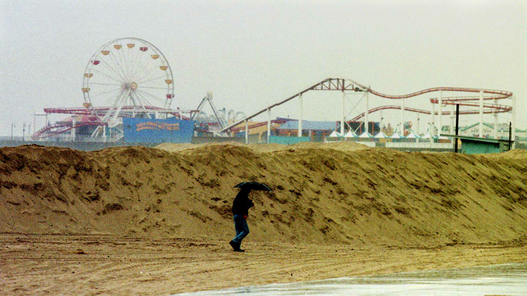 December 5, 1997: A beachcomber walks near a 15-foot sand berm along a beach in Santa Monica as rains from the first El Nino-related storm hits the west coast of the U.S.