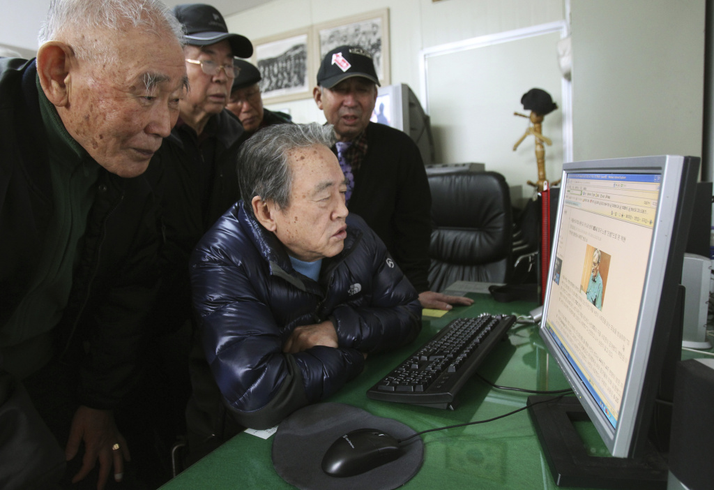 In this Monday, Dec. 2, 2013 photo, Park Young, center, a former member of the Kuwol partisan unit and his comrades look at a website reporting on Merrill Newman, an elderly American tourist detained in North Korea, at the Kuwol partisan unit association office in Seoul, South Korea.  Six decades before he went to North Korea as a curious tourist, Newman supervised the group of South Korean guerrillas during the Korean War who were perhaps the most hated and feared fighters in the North, former members of the group said.