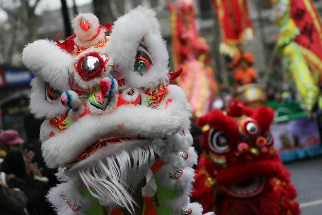 Performers wearing lion costumes dance in a parade for the Chinese Lunar New Year in London on January 29, 2017.