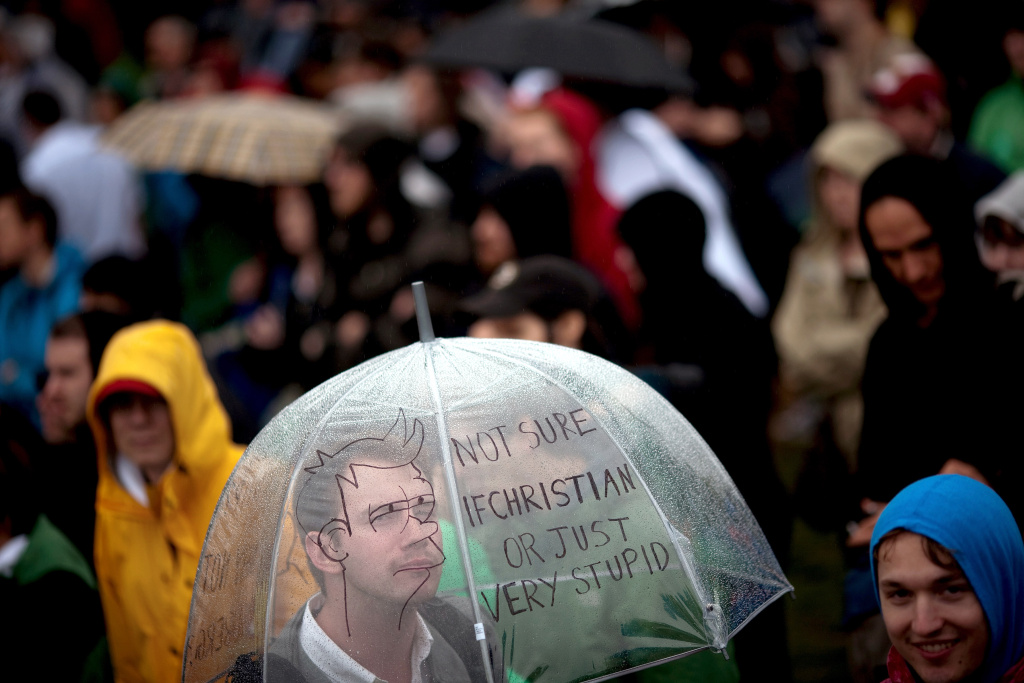 A man looks through an umbrella with a hand-drawn message during the National Atheist Organization's