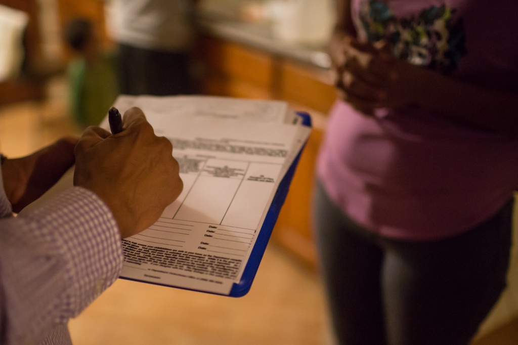 Alfred McCloud fills out paperwork at the end of the home visit. He has decided that the child is safe and can stay with Susana.