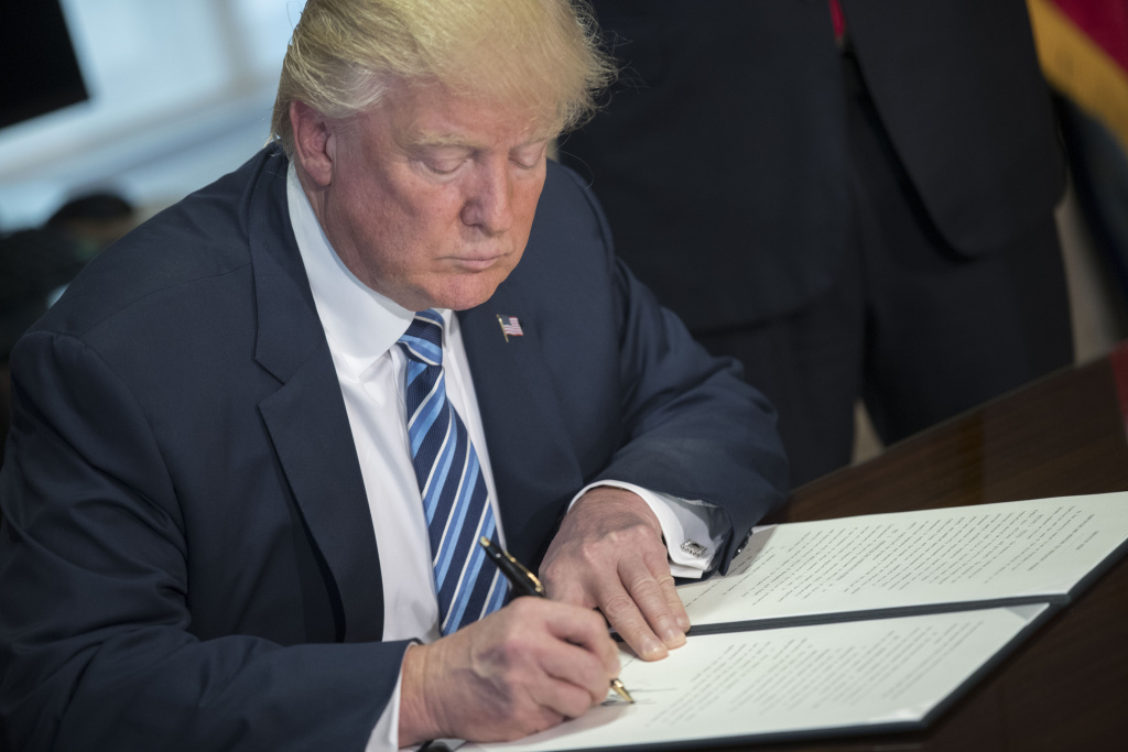 U.S. President Donald Trump signs a financial services Executive Order during a ceremony in the US Treasury Department building on April 21, 2017 in Washington, DC.
