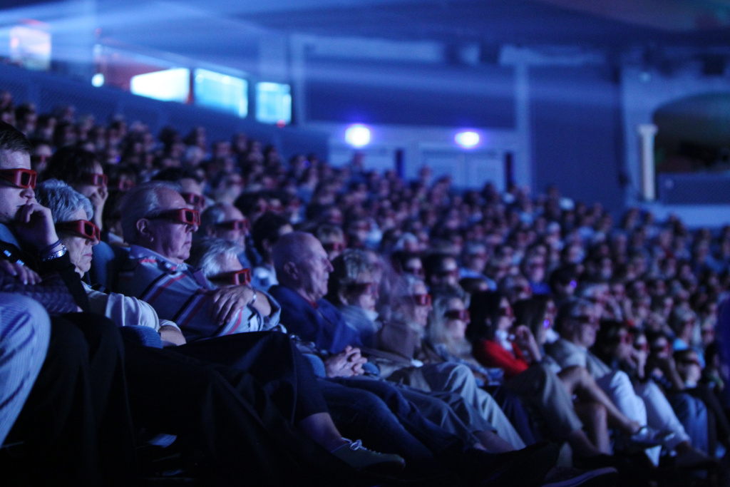 Persons wearing 3D glasses watch the movie