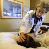 Dr. Martha Twaddle talks to a patient and strokes her hair during a visit at the Midwest Palliative and Hospice CareCenter in Skokie, Ill., in 2012.