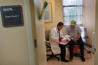 A man gets a checkup from Dr. Olveen Carrasquillo at the University of Miami's Miller School of Medicine in January.