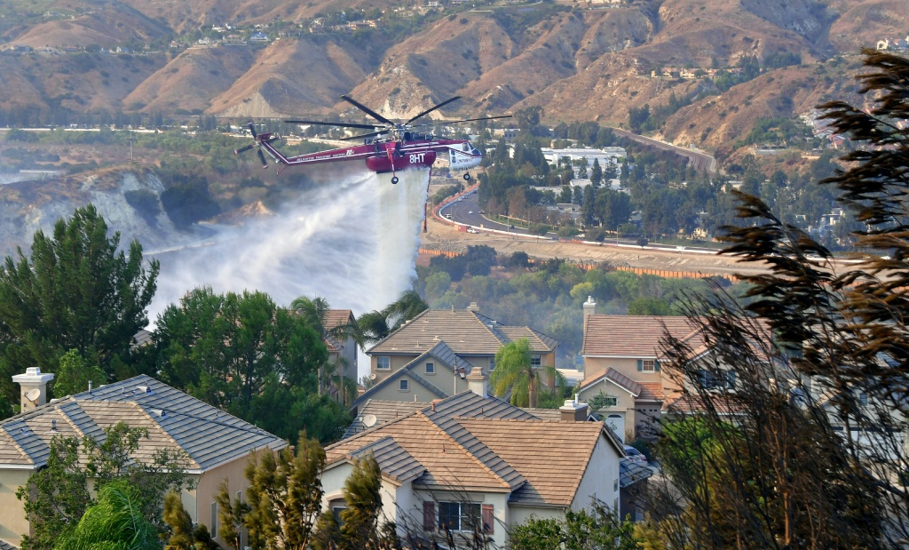 A helicopter drops water near homes in the Anaheim Hills neighborhood on October 9, 2017, after the Canyon Fire 2 spread quickly through the area. Orange County experienced rapid growth in housing construction in fire-prone areas between 1990 and 2010.